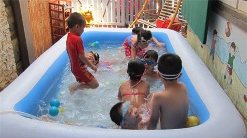 Các em nhỏ vui chơi trong bể bơi tại nhà.