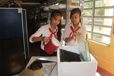 Thu Ngân (bên trái) và Yến Linh đưa nước mặn vào thử nghiệm hệ thống lọc.
