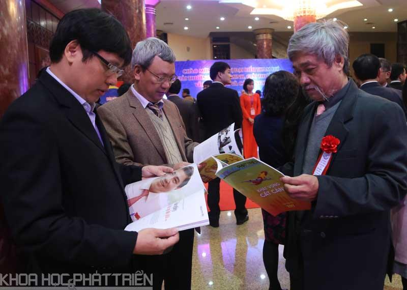 Các đại biểu đọc ấn phẩm Xuân Đinh Dậu của Báo Khoa học và Phát triển trước giờ khai mạc. Ảnh: Loan Lê.