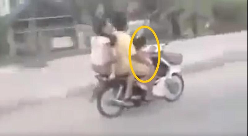 Cận cảnh bé gái 3 tuổi chở 3 người trên chiếc xe máy.