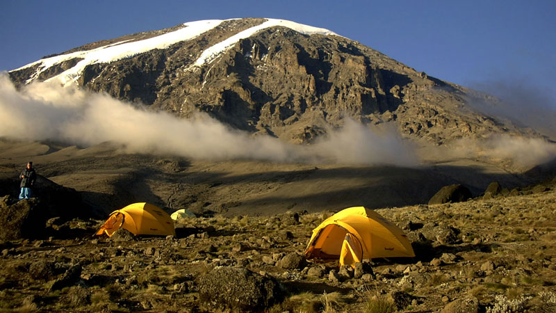 """Ở Kilimanjaro, thật dễ dàng tìm thấy những con đường mòn đông nghịt du khách mà người ta gọi đó là đường """"du khách"""" hay đường """"Coca-Cola"""", đường """"Whiskey""""… bởi vì thứ nước giải khát, rượu bia này được bày bán đầy trong các căn lều dọc bên đường."""
