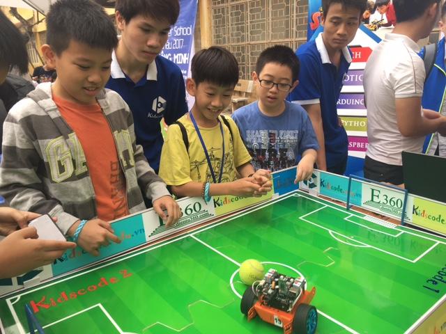 Điều khiển robot để tham gia một trò chơi đá bóng thu hút các bạn học sinh tiểu học.