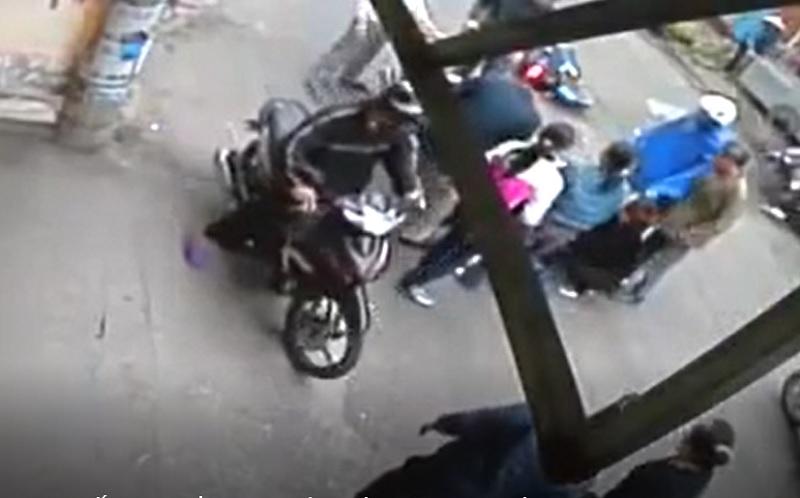 Người dân xung quanh đã kịp thời di chuyển xe máy đè lên người thanh niên.