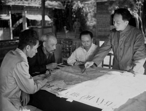 Đại tướng Võ Nguyên Giáp (đứng, bên phải) trình bày với Chủ tịch Hồ Chí Minh và các đồng chí lãnh đạo Đảng, Nhà nước bàn kế hoạch mở chiến dịch Điện Biên Phủ năm 1954 (Ảnh: Tư liệu TTXVN)