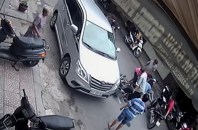 Người dân xung quanh đến giúp đỡ hai người điều khiển xe máy bị tai nạn.