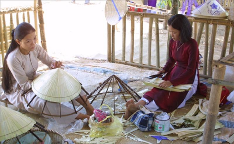 Nghệ nhân làm nón đang khâu lá nón trên khung chằm. Ảnh: Du lịch Việt Nam.