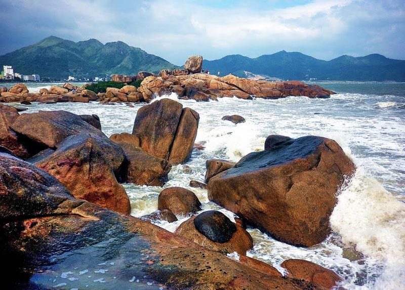 Đi giữa bãi đá còn nhiều tảng đá chồng chất kỳ lạ như cảnh hai hòn đá dựng đứng, giữa có chẹt một hòn đá lớn như cái cổng qua một cụm đá khác. Cụm đá thứ hai có hình dáng một người phụ nữ ngồi trông ra biển - được đặt một cái tên có ý nghĩa gần gũi với Hòn Chồng - đó là Hòn Vợ, cụm đá này ít được du khách để ý hơn. Ảnh: Kinh Dinh.