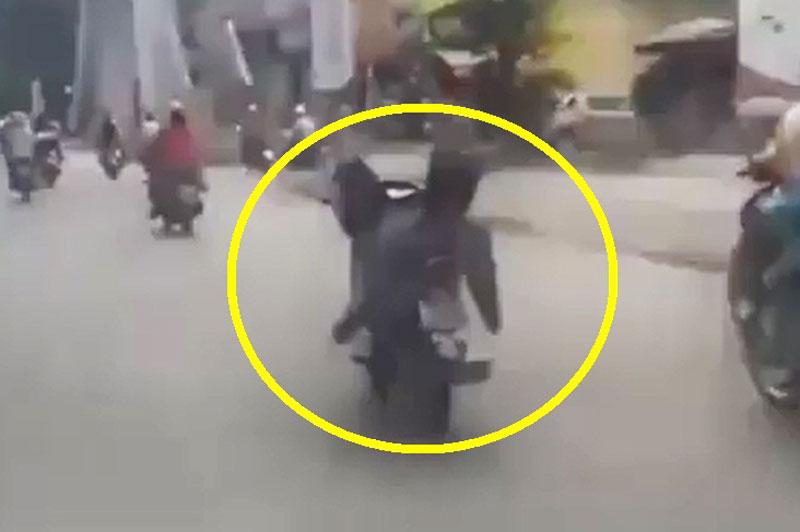 Nam thanh niên lái xe máy bằng chân.