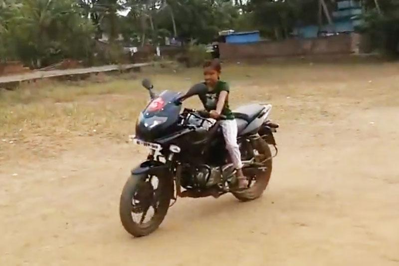 Bé gái điều khiển môtô trên sân bóng.