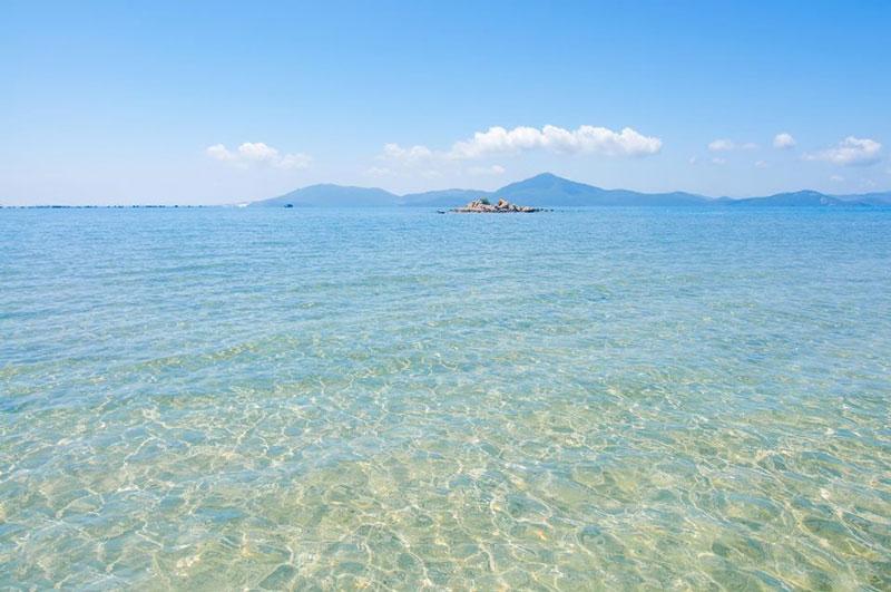 Sáu giờ sáng hàng ngày, thủy triều rút, con đường cát xuất hiện, dài khoảng 500m, rộng từ 8m ở gần đảo, rồi nhỏ dần ra xa còn khoảng 2 - 3m. Khi thủy triều dâng, đường nằm chìm dưới mặt biển khoảng 1m. Ảnh: Hang Dinh.