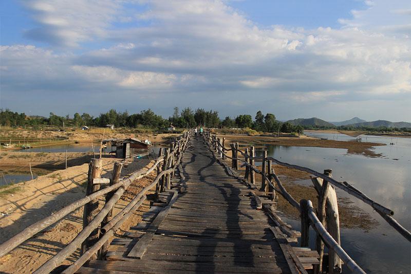 Mặt và trụ cầu được làm hoàn toàn từ gỗ ván. Trong khi đó, thành cầu chỉ nối với nhau bằng những thanh tre. Tuy không đảm bảo độ an toàn nhưng vì sự tiện dụng của nó, nhiều người vẫn đi lại qua chiếc cầu này. Ảnh: Hau Nguyen.