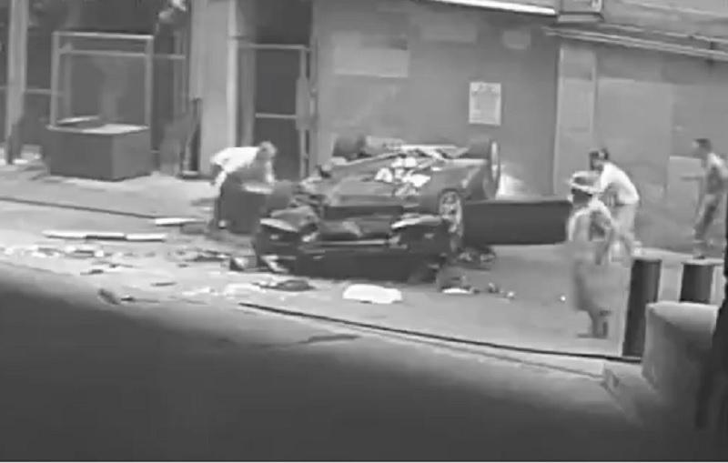 Người dân xung quanh chạy đến cứu giúp tài xế mắc kẹt trong chiếc ôtô vừa rơi nát bét.