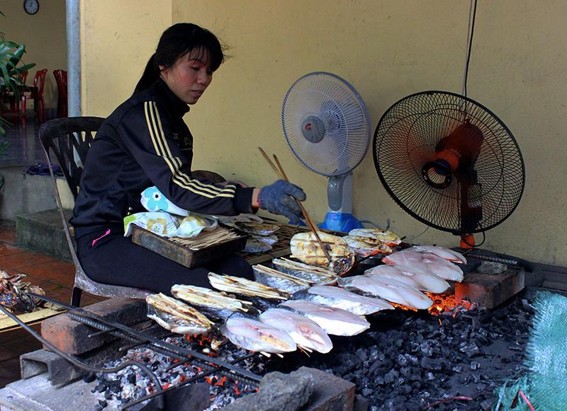 Một hộ sản xuất ở Cửa Lò đang nướng cá thu. Ảnh: Quảng An