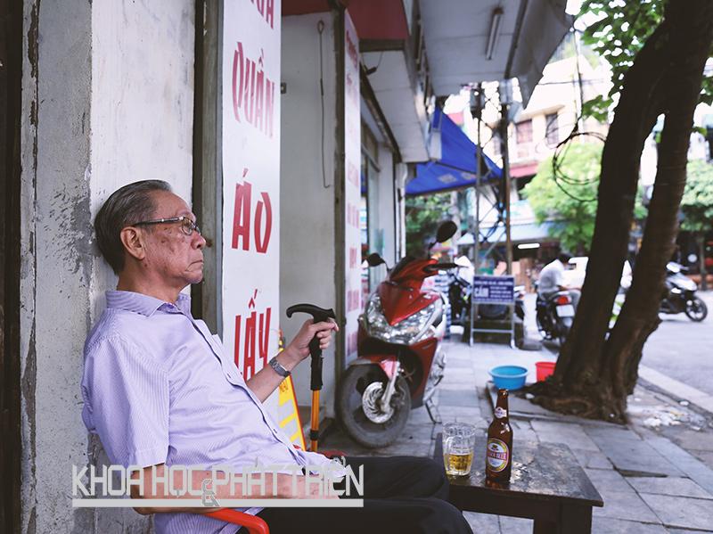Một cụ già vừa nhâm nhi cốc bia vừa ngắm phố trên vỉa hè phố Đào Duy Từ, Hà Nội. Ảnh: Loan Lê
