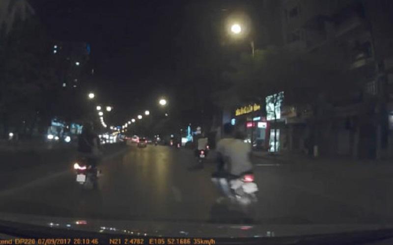 Hai thanh niên không đội mũ bảo hiểm, điều khiển xe máy với tốc độ cao.