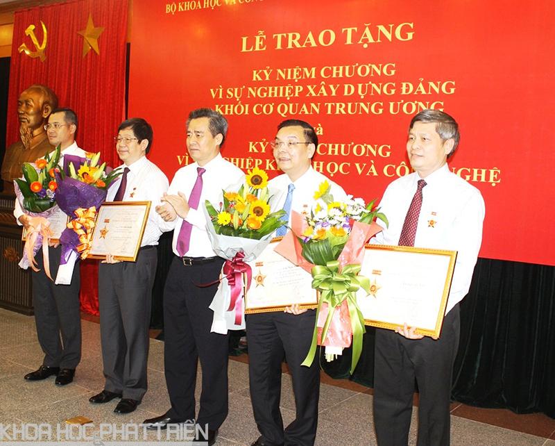 Ông Nguyễn Quang Dương - Bí thư Đảng ủy khối trao Kỷ niệm chương cho 04 đồng chí trong Lãnh đạo Bộ KH&CN