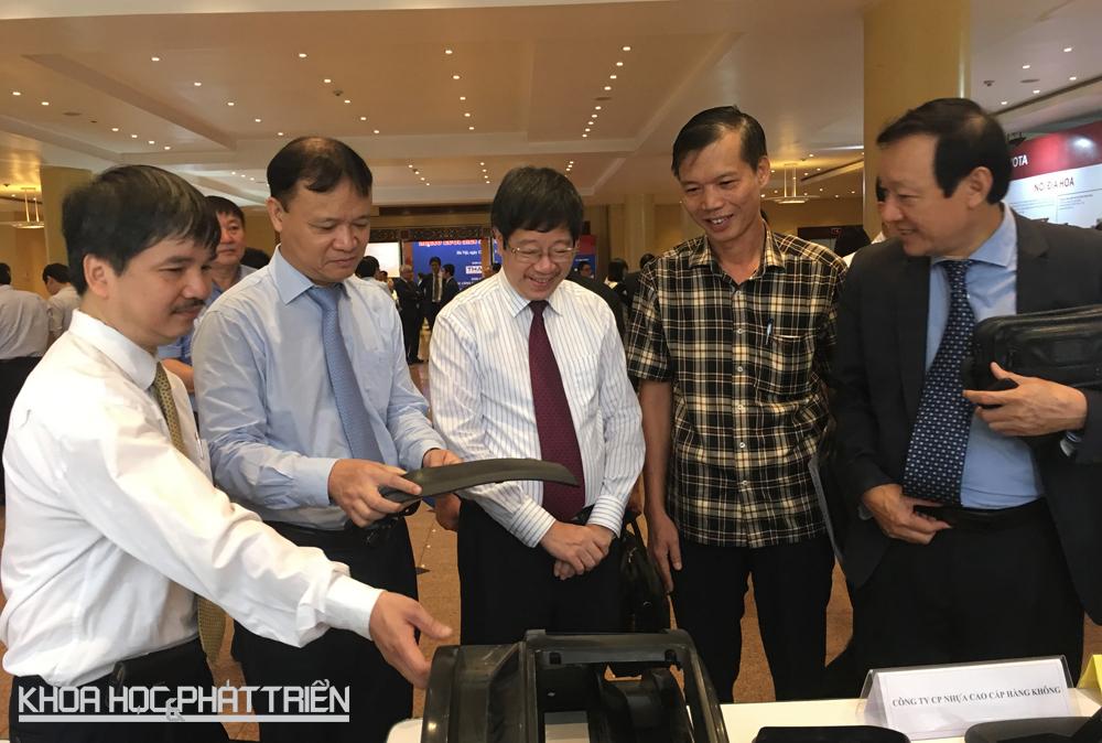 Thứ trưởng Bộ Công Thương Đỗ Thắng Hải (áo xanh) và Thứ trưởng Bộ KH&CN Trần Quốc Khánh (áo kẻ sọc trắng) xem triển lãm trưng bày linh kiện ôtô. Ảnh: NV