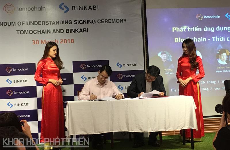 Ông Quân Lê (áo hồng) và ông Long Vương (áo đen) ký biên bản thỏa thuận hợp tác. Ảnh:NV