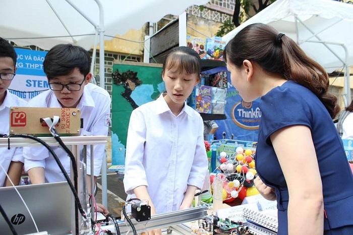 Các em học sinh trường THPT An Dương giải thích cơ chế hoạt động của máy in 3D cho các phụ huynh nghe.