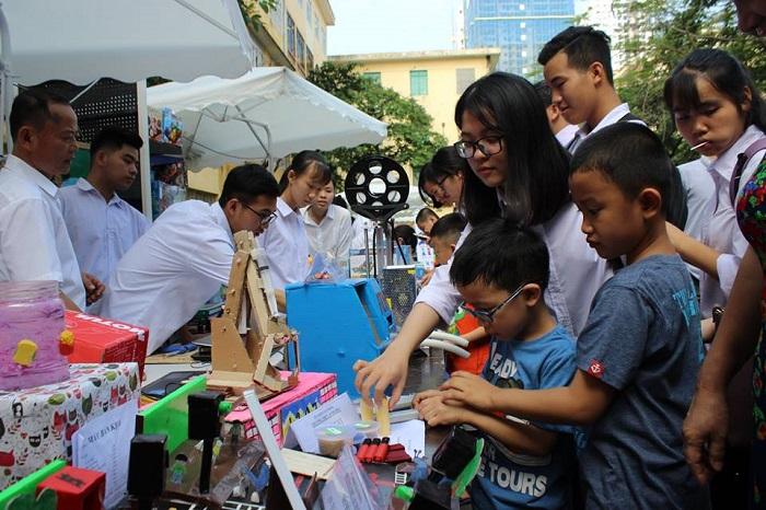 Các bạn nhỏ thích thú thử điều khiển mô hình cần cẩu bằng bìa cứng của các anh chị học sinh trường THPT An Dương.