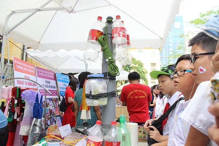 Các em nhỏ lắng nghe giải thích về dự án STEM của các bạn học sinh lớp 9 trường THPT Nguyễn Thị Minh Khai, huyện Bắc Từ Liêm, Hà Nội: hệ thống lọc nước sử dụng hạt nano có thể được dùng cho những khu vực nước bị ô nhiễm, vùng bão lũ.