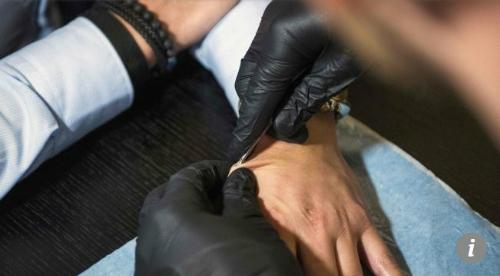 Đưa con chip vào tay người tình nguyện. Ảnh: AFP.