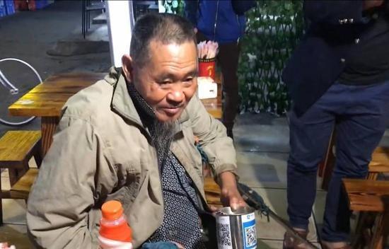 Một cụ ông với QR Code dán trên chiếc lon xin ăn - Ảnh: China Daily/Asia News Network