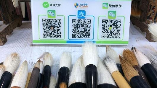 Một nơi bán bút lông có cả tài khoản WeChat (ngoài cùng bên trái), và tài khoản AliPay (ở giữa) cho khách tuỳ chọn cách trả - Ảnh: Evelyn Cheng/CNBC