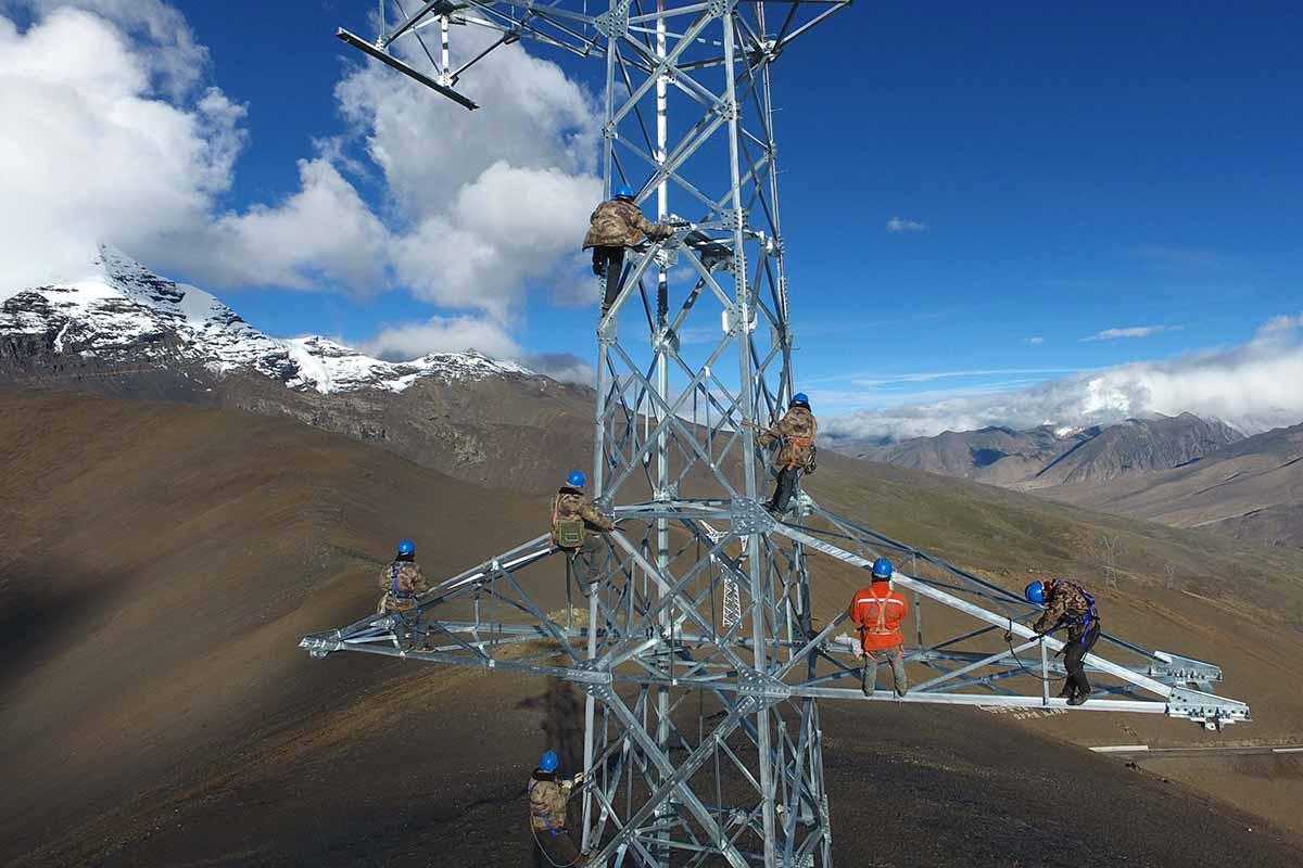 Công nhân Trung Quốc đang xây dựng tháp truyền tải điện ở độ cao 5.548 mét trên đỉnh Mengdala thuộc huyện Lạc Trát (Luozha), địa khu Sơn Nam (Lhoka), khu tự trị Tây Tạng. Ảnh: STR/AFP.