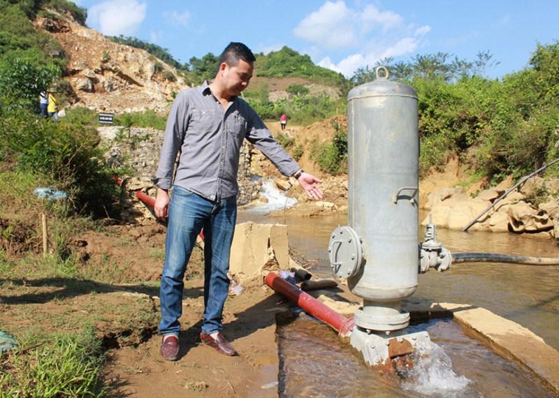 Một nhà nghiên cứu thuộc dự án giới thiệu bơm tự áp đưa nước từ suối về bể chứa ở trường. Ảnh: Minh Đức/Phụ nữ Việt Nam.