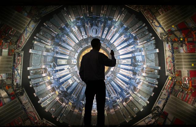 Một người đứng trước bức tranh máy gia tốc hạt tại Bảo tàng khoa học London. Ảnh: Genk