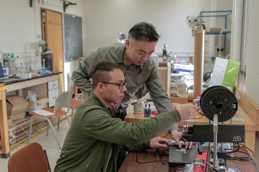 Kỹ sư kiểm nghiệm chính Xudong Wang (đứng) và Sinh viên tốt nghiệp Guang Yao (ngồi) đang điều chỉnh máy in 3D để chế tạo thiết bị cấy ghép giảm cân. (Nguồn: ĐH Wisconsin-Madison)