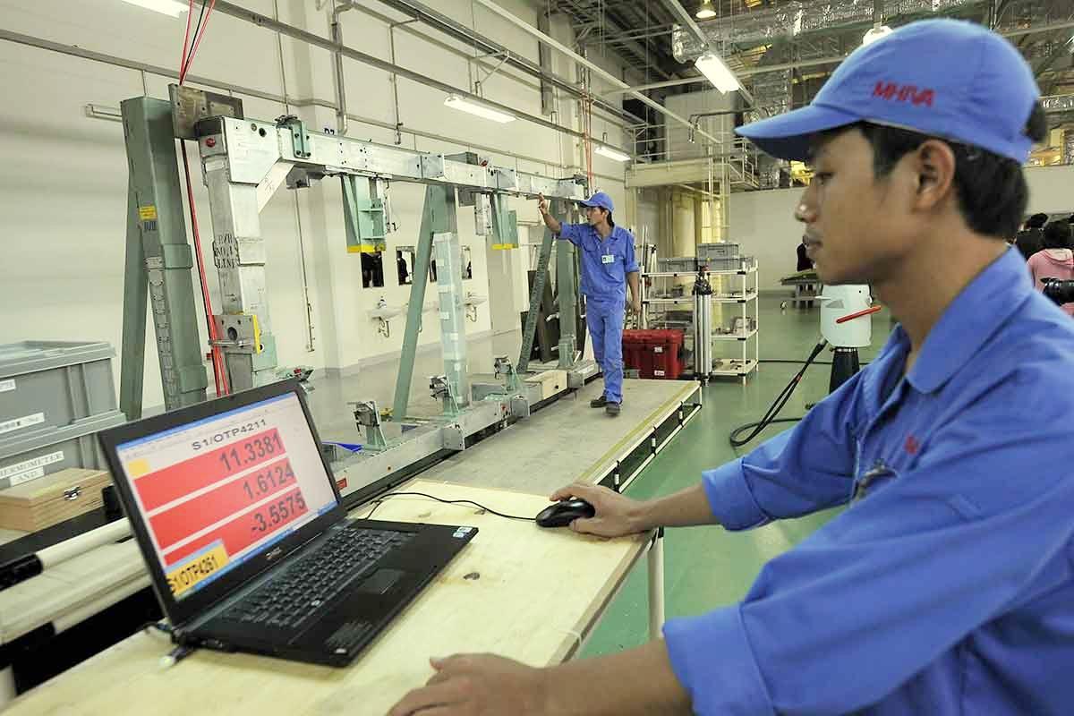 Kỹ thuật viên của Công ty Công nghiệp nặng Mitsubishi(MHI) đang làm việc tại dây chuyền sản xuất ở Khu công nghiệp Thăng Long, Hà Nội. Ảnh: AFP