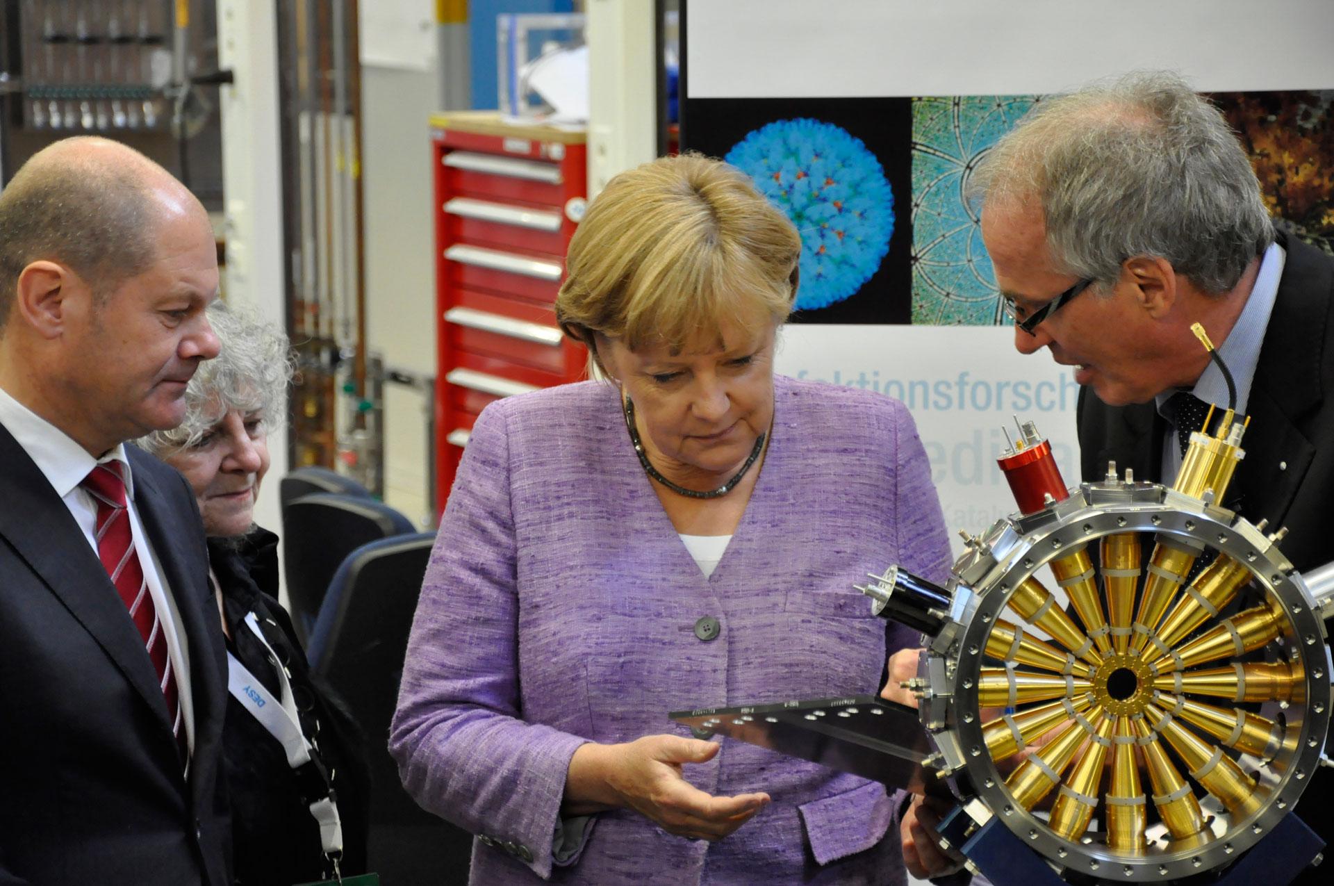 Giám đốc Trung tâm Máy gia tốc DESY Helmut Dosch giải thích về một thiết bị được sử dụng trong nghiên cứu về phóng xạ với Thủ tướng Đức Angela Merkel. Nguồn: Bundeskanzlerin