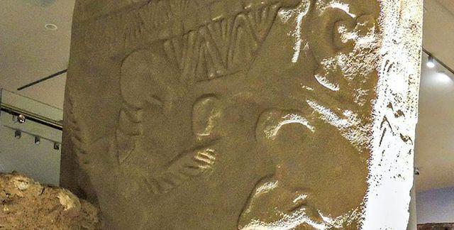 Phiến đá cổ xưa với những hình chạm khắc.