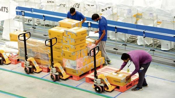 Nhiều công nhân làm việc tại kho hàng của Amazon đang lo ngại mất việc vào tay robot. Ảnh: Yahoo Finance.