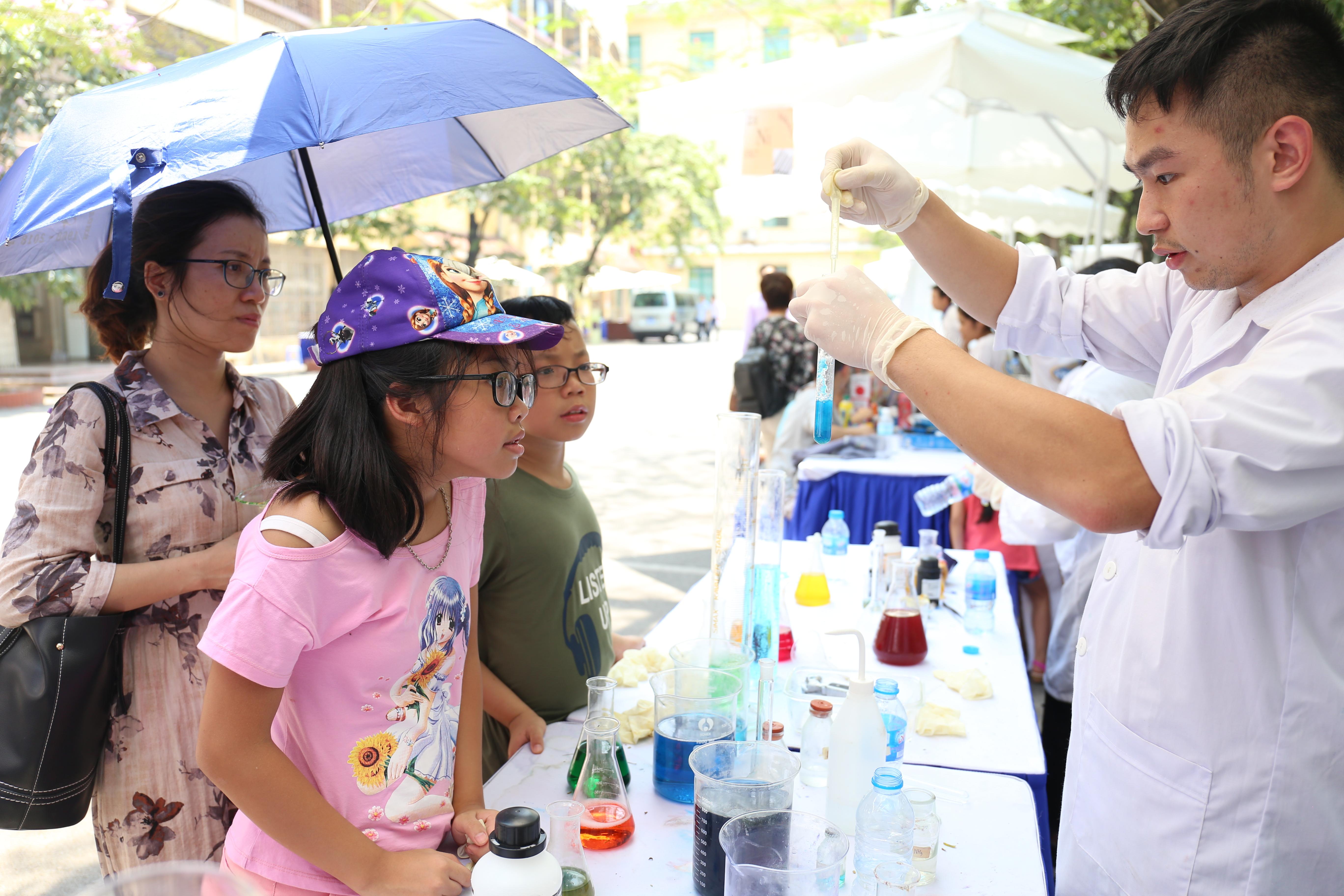 """Các em nhỏ được xem và tận tay làm thí nghiệm với một số hóa chất thường dùng trong phòng thí nghiệm như đồng sulfate. """"Lúc nào các em cũng phải cẩn thận, làm nhẹ nhàng và đeo găng tay để bảo vệ mình nhé"""", các anh chị sinh viên hướng dẫn những em lần đầu tiên được dùng bộ hóa chất."""