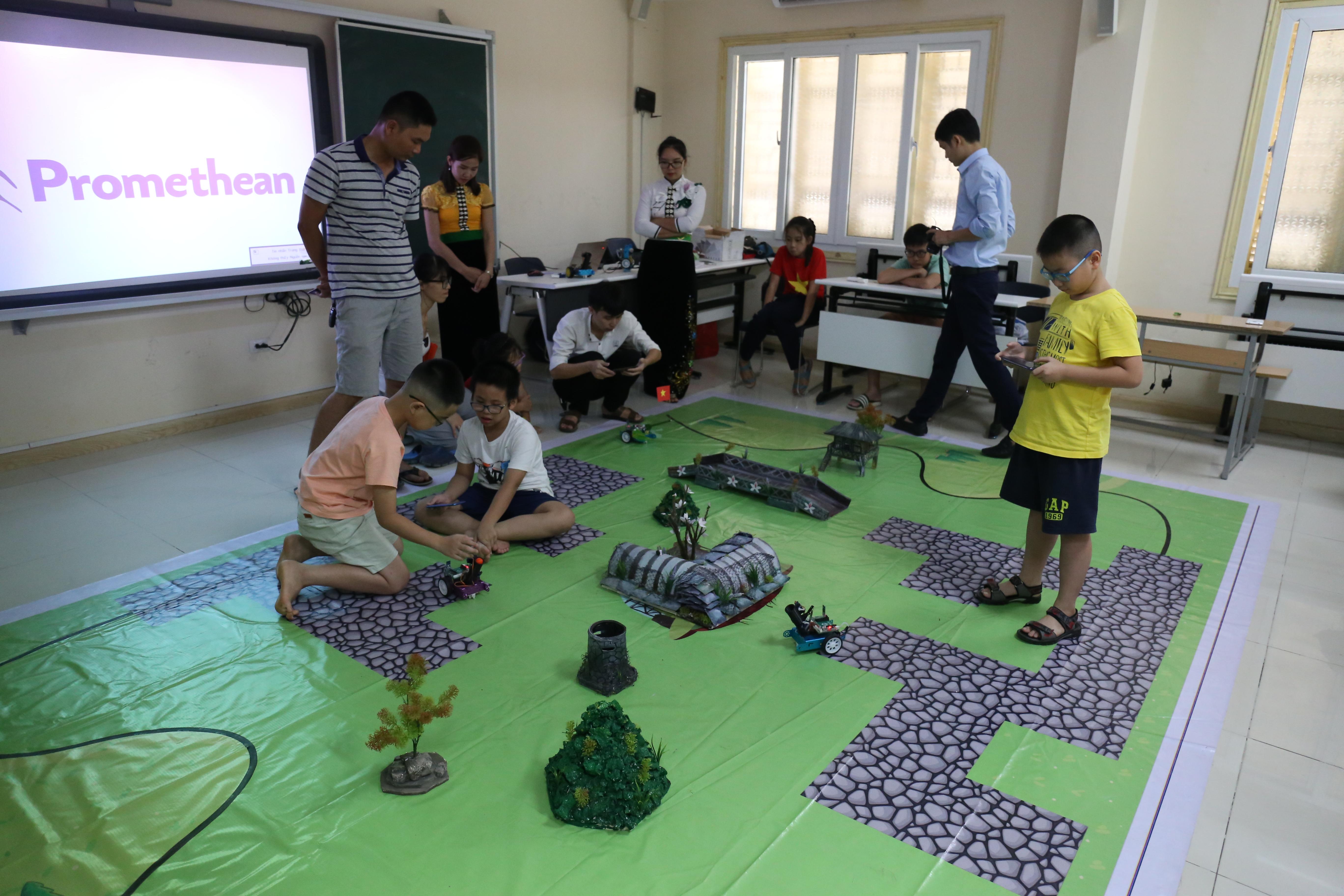"""""""Mô hình của chúng tôi tái hiện trận Điện Biên Phủ với các xe robot điều khiển từ xa,"""" cô Đào Thị Loan, Bí thư chi đoàn trường tiểu học Bế Văn Đàn, TP. Điện Biên, giới thiệu. Đây là kết quả mà các thầy cô ở trường tạo ra sau 2 ngày được Liên minh STEM tập huấn và dạy lại cho học sinh. """"Các em rất hào hứng, em nào cũng muốn sờ vào robot và nhiều em muốn lập trình cho chúng nữa"""". Nhà trường mới có khoảng gần 10 robot do được tài trợ, ước tính mỗi robot trị giá 1,5 triệu đồng."""