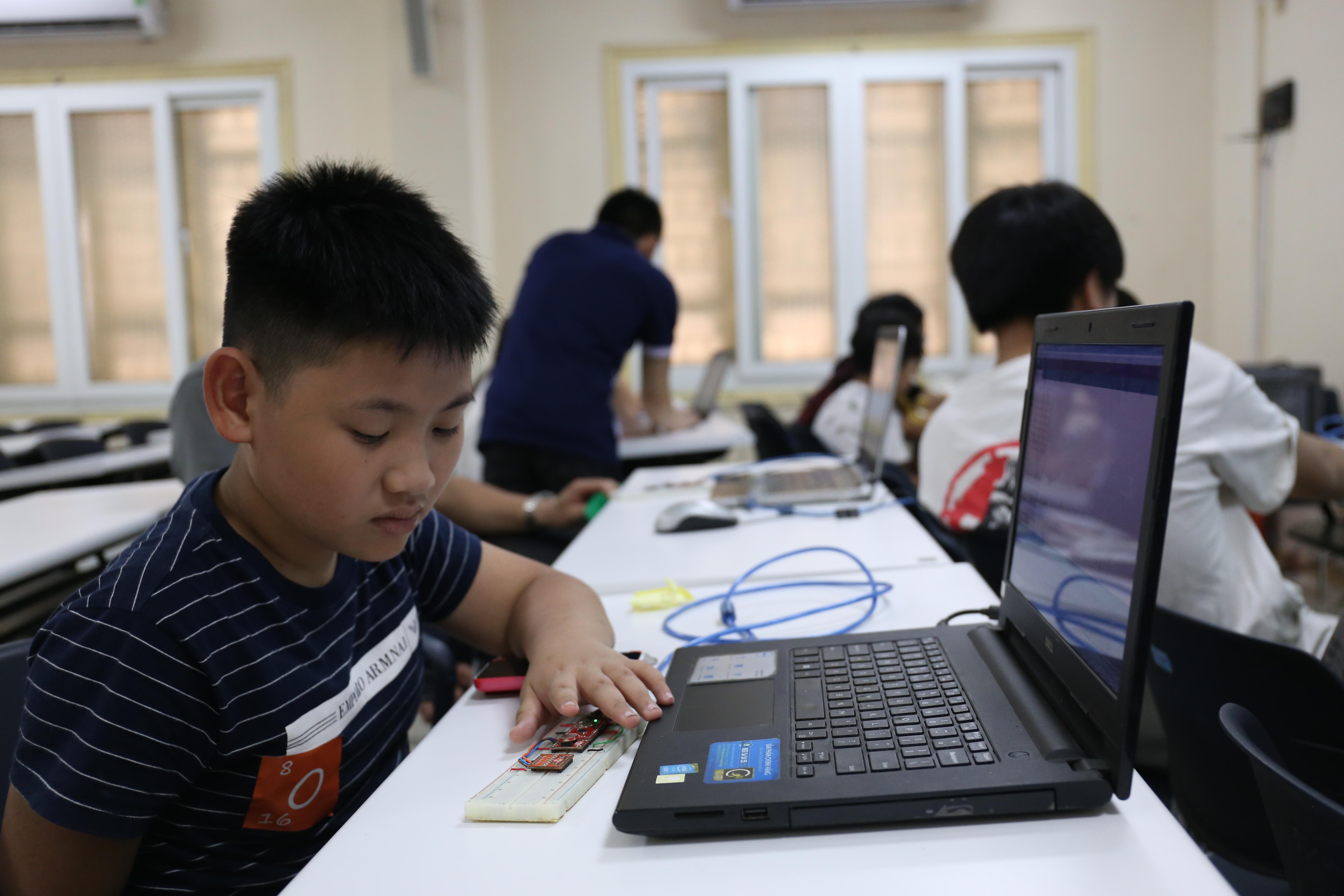 """Lập trình cho robot di chuyển hay cho cảm biến phát sáng đều không khó. Các em có thể sử dụng phần mềm trực quan để kéo những khối lệnh thành một cụm sơ đồ, hay dùng các nền tảng nguồn mở Arduino để viết câu lệnh theo ngôn ngữ lập trình. Em Nguyễn Đặng Trường Giang, lớp 6, trường THCS Tây Sơn, quận Hai Bà Trưng, Hà Nội, hào hứng khoe khi tham gia lớp học lập trình cho robot của Kidscode, """"Đây là lần đầu tiên em được lập trình 'cool' như thế này. Hồi cấp 1, bọn em cũng học nhưng chỉ để di chuyển hình vẽ trên máy tính thôi, còn ở đây có cả đèn bật/tắt khi em che ánh sáng đi""""."""