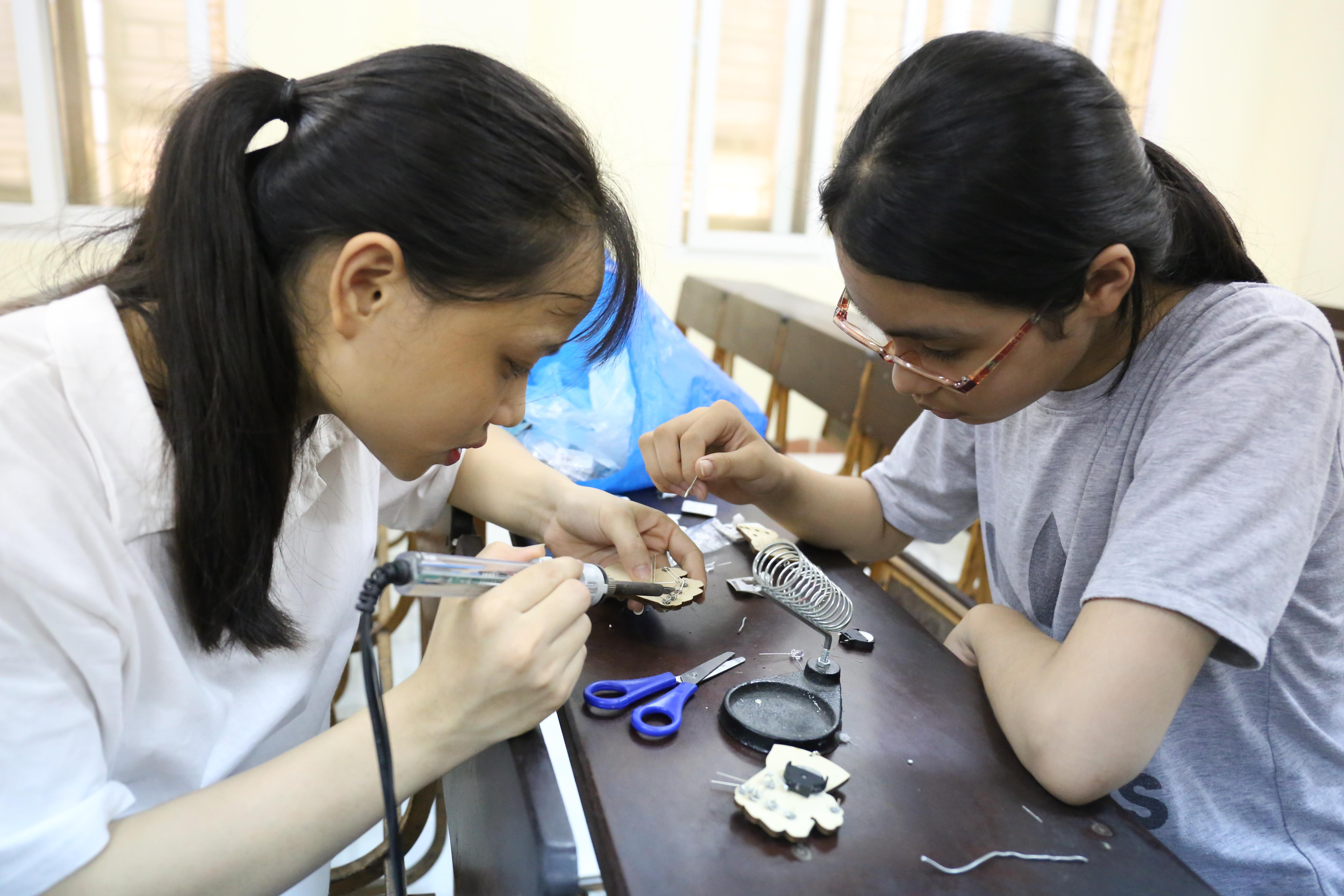Cơ khí kỹ thuật không chỉ dành cho con trai mà cả con gái nữa. Tại lớp học STEM, các em dùng mỏ hàn để hàn các đèn Led vào mạch điện để làm Găng tay Thanos. Ai khéo tay làm xong sản phẩm đều có thể mang móc khóa gắn găng tay về nhà làm kỷ niệm.