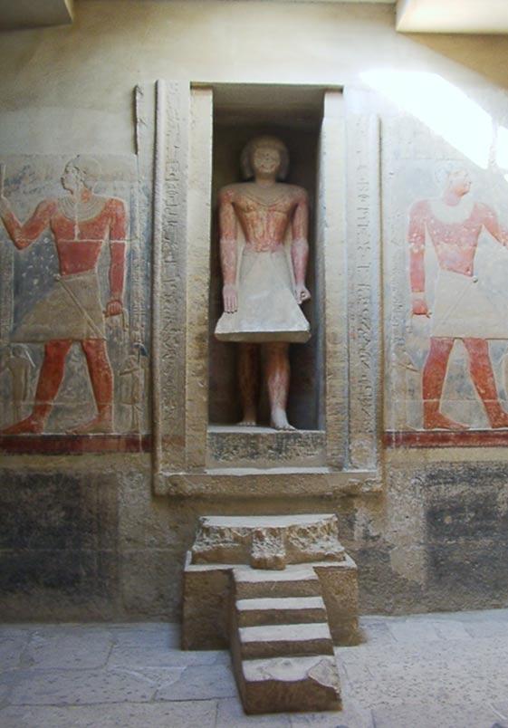 Bức tượng có kích thước như người thật đang bước qua cánh cửa giả. Ảnh: Wikmedia