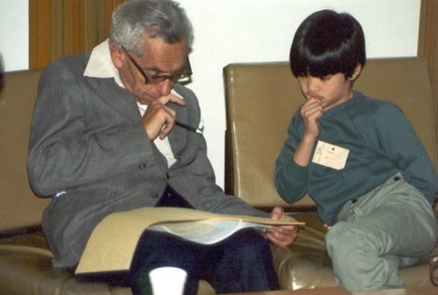 """Paul Erdös (1913 – 1996), nhà Toán học nổi tiếng người Hungary, đang xem bài của Terence Tao trước khi trao phần thưởng 500 USD cho Terence Tao (10 tuổi). Chính Paul Erdös đã viết thư giới thiệu Terence Tao cho ban tuyển chọn sinh viên Tiến sĩ của Đại học Princeton. Trong thư có câu: """"Tôi tin chắc rằng trong vài năm tới chàng sinh viên này sẽ trở thành một trong những nhà Toán học hàng đầu thế giới."""" Và Erdös đã không sai."""