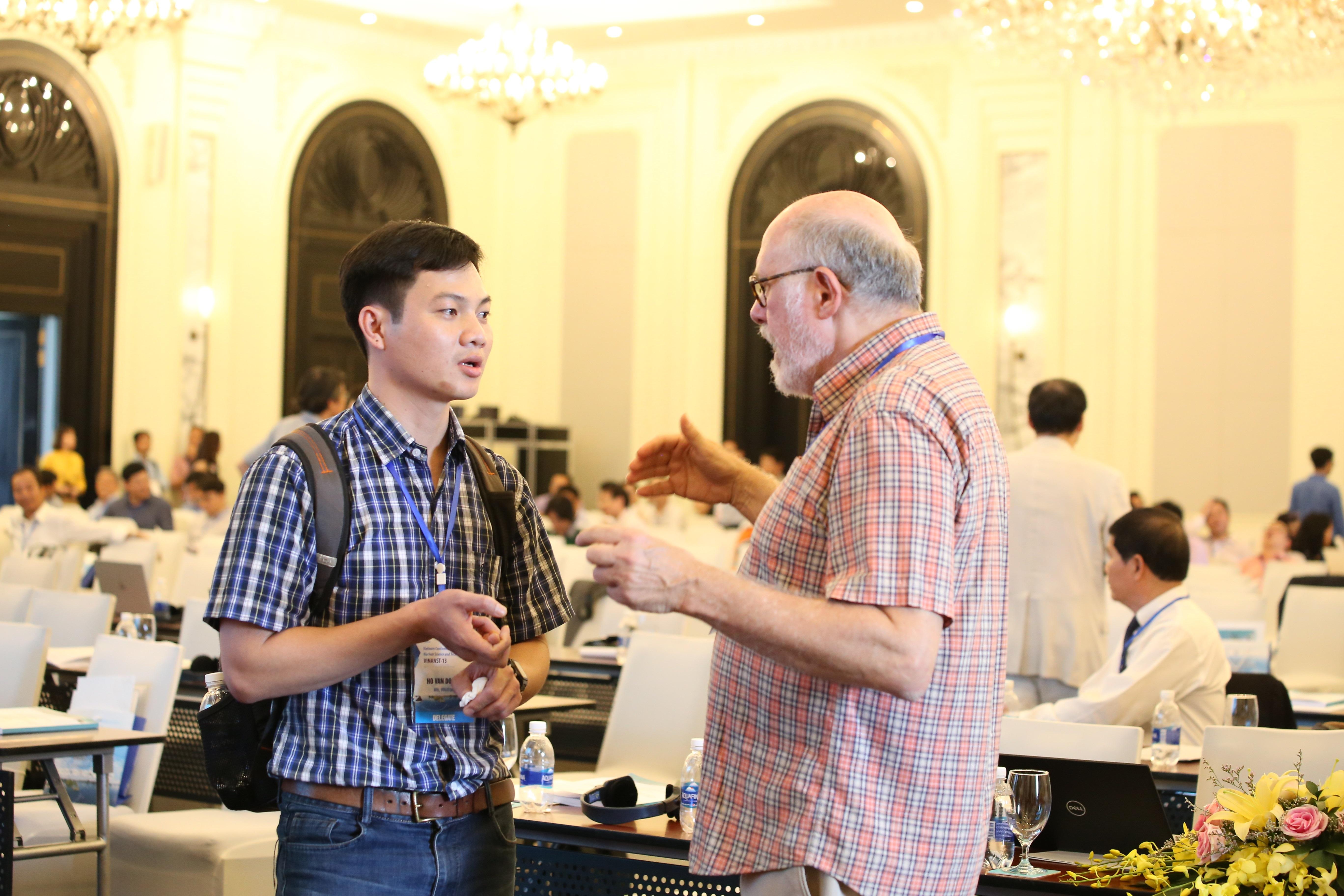 Nhà nghiên cứu trẻ Hồ Văn Doanh (Viện nghiên cứu hạt nhân) trao đổi với giáo sư Sheldon Lansberger (trường Đại học Texas, Mỹ) bên lề Hội nghị.