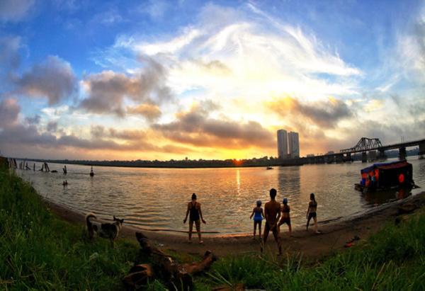 """""""Đón mặt trời"""" - Tác giả Nguyễn Quốc Vượng Bãi giữa sông Hồng, nơi người dân thường đến rất sớm tập thể dục, đón bình minh và ngụp lặn trong dòng nước phù sa, bất kể đông hay hè. Một góc không gian công cộng hiếm hoi cho con người hoàn toàn về với tự nhiên."""