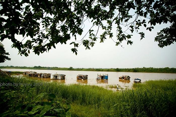 """""""Xóm ven sống"""" - Vũ Quang Huy. Vài năm trước, cách Bờ Hồ chưa đầy 1 km là xóm chài ven sông. Để ra được """"xóm"""", phải đi qua nhiều con ngõ nhỏ hun hút, ngóc ngách. Nơi đây các ngôi """"nhà"""" đều ở trạng thái nửa nổi nửa chìm để phòng mỗi năm đến mùa lũ về xóm lại bập bềnh bên mép nước. Xóm chỉ có khoảng hơn chục nóc nhà với cư dân là lao động nghèo các tỉnh về Hà Nội làm thuê. Mùa nước lên cũng là lúc các cư dân nơi đây vất vả nhất, """"nhà"""" đã được neo lại và nổi trên sông để tránh...trôi đi, tuy vậy việc đi lại cũng không hề dễ dàng mà hoàn toàn phụ thuộc vào những con thuyền nhỏ hoặc trên các phao nổi được neo giữa bờ và """"nhà"""". Theo thời gian, các """"ngôi nhà"""" này cũng đã dần biến mất bởi sự bất tiện và phần vì nước sông ngày càng cạn. Đa phần họ cũng đã di chuyển lên bờ hay tìm cho mình những nơi cư ngụ ổn định hơn. Những hình ảnh này giờ đây lưu lại ký ức về một thời """"ngụ cư"""" của những thân phận trôi dạt."""