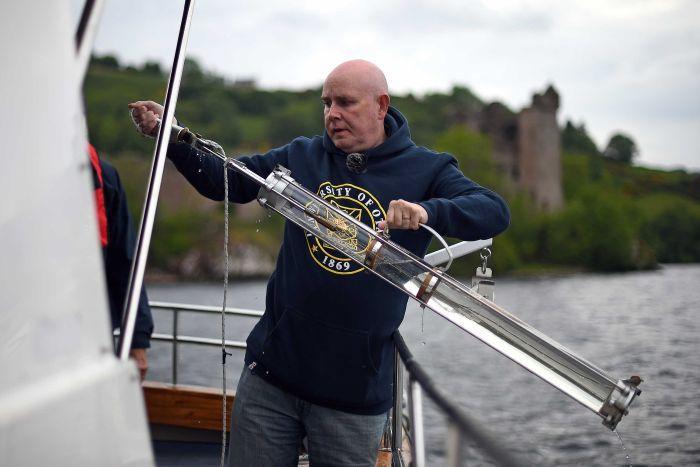 Neil Gemmell lấy mẫu nước tại hồ Loch Ness. Ảnh: AFP.