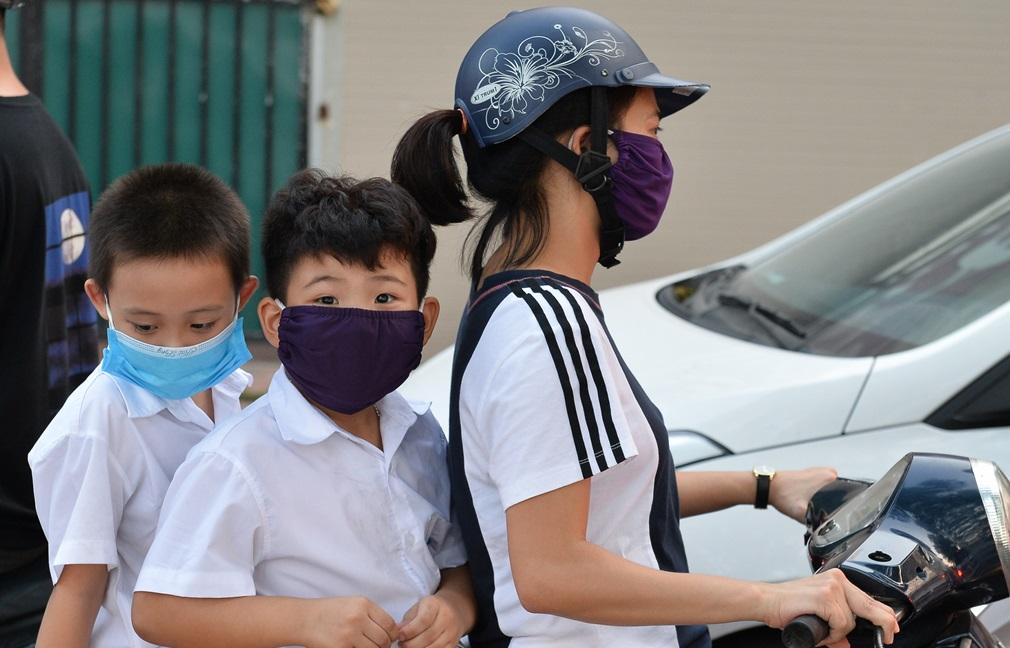 Chất lượng không khí ảnh hưởng đến chất lượng cuộc sống của người dân. Trong ảnh, trẻ em đeo khẩu trang khi ngồi sau xe máy trên đường Nguyễn Đình Thi, Hà Nội chiều 30/9. Ảnh: Việt Hùng/Zing