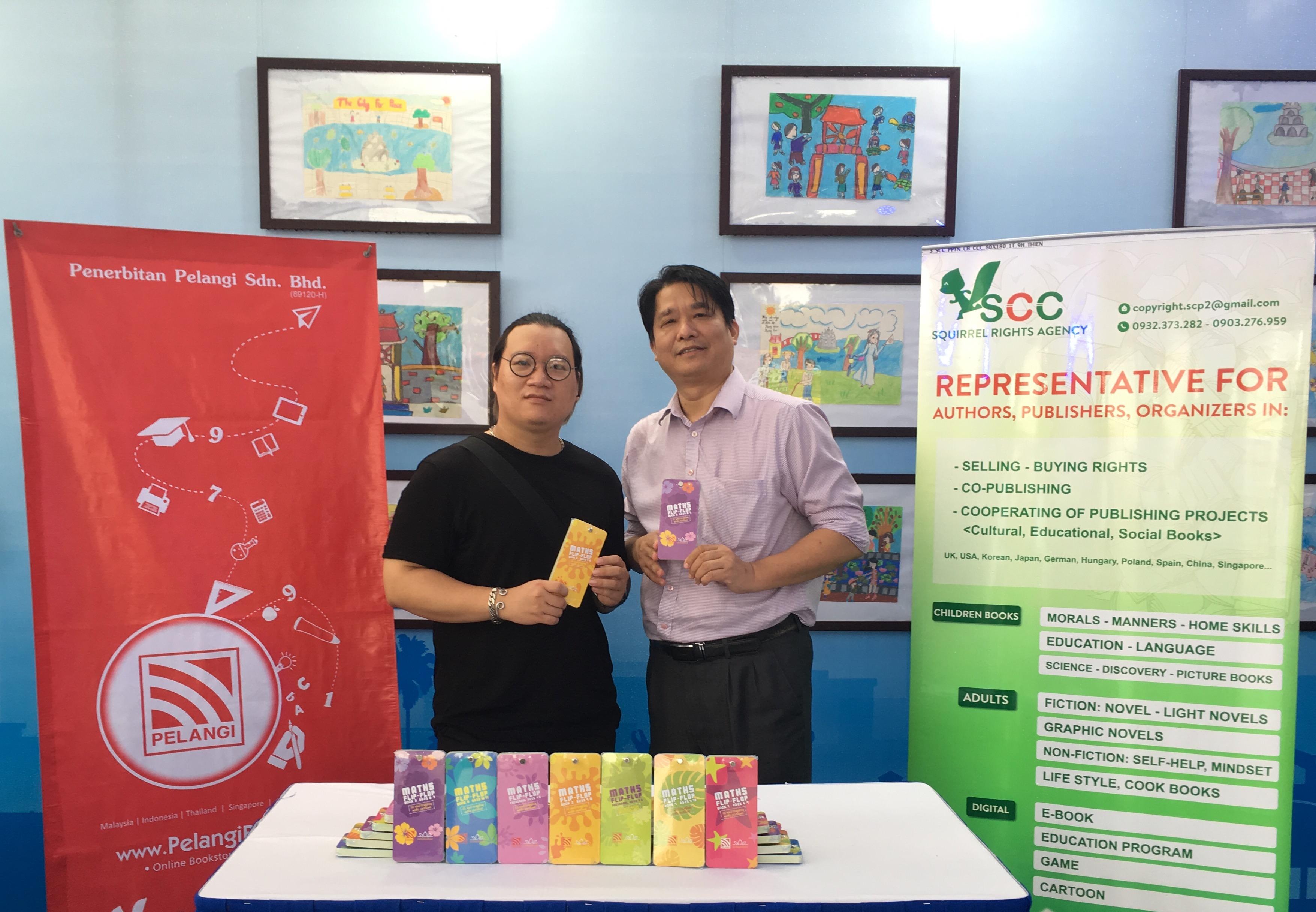 """Ông Đỗ Hoàng Sơn (phải) và họa sĩ Bùi Tuấn Linh bên phiên bản bộ sách """"Em thích giỏi Toán"""" do Malaysia mua bản quyền của Công ty Long Minh tại Hội Sách Hà Nội 2019. Ảnh: NVCC"""