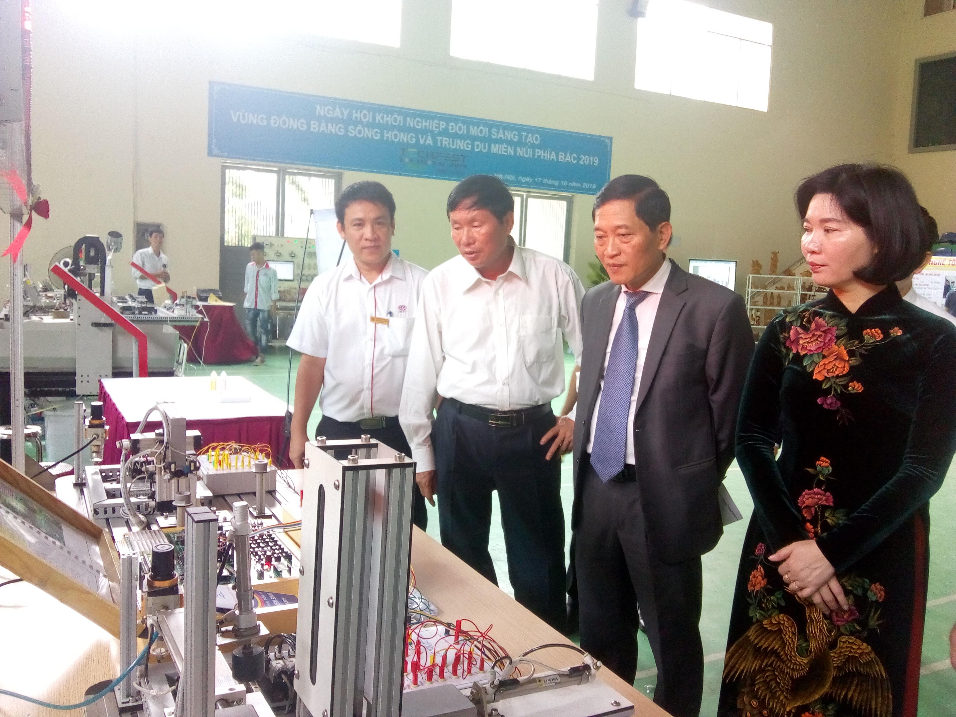 Thứ trưởng Bộ KH&CN Trần Văn Tùng (trái) cùng các đại biểu tham quan gian hàng triển lãm của các trường cao đẳng nghề | Ảnh: Ngô Hà
