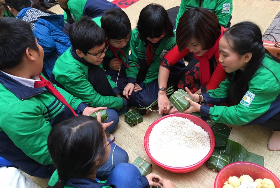 Các em học sinh trường THCS Nguyễn Tri Phương (Ba Đình, Hà Nội) tham gia hoạt động gói bánh chưng gửi tặng trẻ em mồ côi vùng cao Hà Giang. Ảnh: dangcongsan.vn